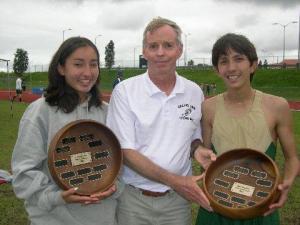 Honokaa's Tia Greenwell & Jake Shiraki are awarded koa bowls for being the top 1500 meter runners in the BIIF